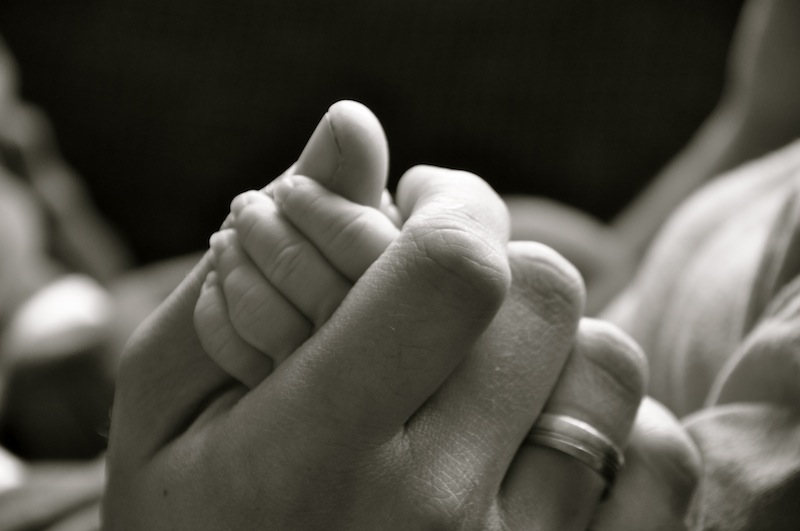 Mother holding baby hands